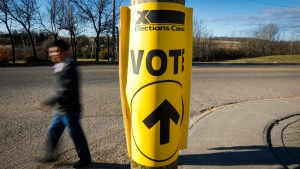 A voter walks past a sign directing voters to a polling station for the Canadian federal election in Cremona, Alta., Monday, Oct. 19, 2015. THE CANADIAN PRESS/Jeff McIntosh