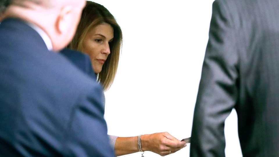 Lori Loughlin enters through the back door at federal court Tuesday, Aug. 27, 2019, in Boston, for a hearing in a nationwide college admissions bribery scandal. (AP Photo/Steven Senne)