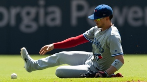 Toronto Blue Jays second baseman Cavan Biggio recovers a a fielding error by third baseman Brandon Drury on a ball hit by Atlanta Braves' Dansby Swanson during the third inning of a baseball game Monday, Sept. 2, 2019, in Atlanta. Josh Donaldson and Ozzie Albies scored on the play. (AP Photo/John Amis)