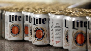 In this March 11, 2015 file photo, newly-filled and sealed cans of Miller Lite beer move along on a conveyor belt, at the MillerCoors Brewery, in Golden, Colo.  (AP Photo/Brennan Linsley, File)