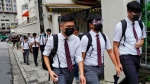 Students wearing masks, walk along with their formal uniforms near Diocesan Boys' School in Hong Kong, Friday, Sept. 6, 2019. (AP Photo/Vincent Yu)