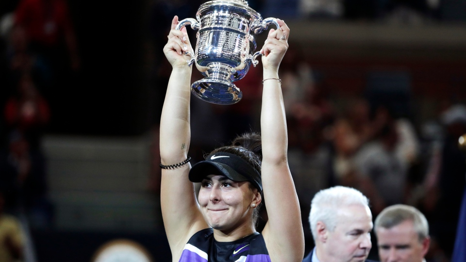 Bianca Andreescu, of Canada, holds up the championship trophy after defeating Serena Williams, of the United States, in the women's singles final of the U.S. Open tennis championships Saturday, Sept. 7, 2019, in New York. (AP Photo/Adam Hunger)