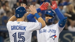 Toronto Blue Jays' Teoscar Hernandez, right, high fives with teammate Randal Grichuk after hitting a two-run home run against the Boston Red Sox in the fifth inning of their American League MLB baseball game in Toronto on Wednesday, September 11, 2019. THE CANADIAN PRESS/Fred Thornhill