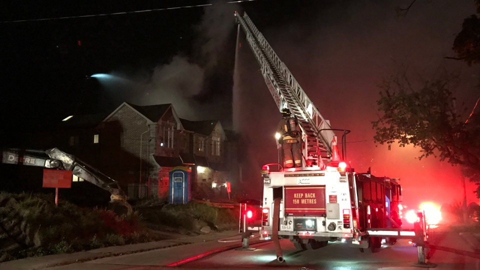 A fire truck sprays water on a home under construction on Westbourne Avenue on Sept. 13, 2019. (Mike Nguyen/CP24)