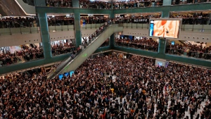 """In this Wednesday, Sept. 11, 2019, file photo, local residents sing a theme song written by protesters """"Glory be to thee"""" at a shopping mall in Hong Kong. Hong Kong Chief Executive Carrie Lam reassured foreign investors Wednesday that the Asian financial hub can rebound from months of protests, despite no sign that the unrest will subside. (AP Photo/Vincent Yu, File)"""