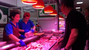 In this Wednesday, Sept. 11, 2019, photo, clerks help a customer shop for pork at a meat market in Beijing. Chinese families are having to rethink menu options as pork prices soar despite government efforts to rebuild herds decimated by African swine fever and large-scale closures of pig farms for environmental reasons. (AP Photo/Fu Ting)