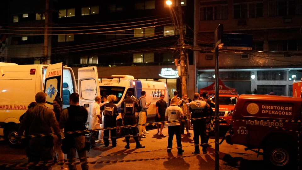 Personnel stand outside the hospital where a fire forced staff to evacuate in Rio de Janeiro, Brazil,Thursday, Sept. 12, 2019. The fire forced staff to hastily evacuate patients and temporarily settle some on sheets and mattresses in the street while firefighters fought the blaze. (AP Photo/Leo Correa)