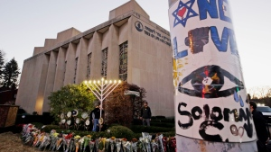This Dec. 2, 2018, file photo shows a menorah at a memorial outside the Tree of Life Synagogue, where Robert Bowers killed worshippers in an Oct. 27 shooting, as people prepare for a celebration service at sundown on the first night of Hanukkah in the Squirrel Hill neighborhood of Pittsburgh. (AP Photo/Gene J. Puskar, File)