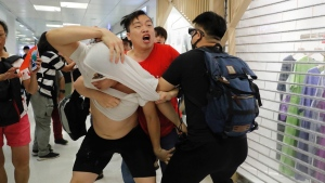 A Pro-China supporter, in red, and anti-government protesters fight at Amoy Plaza in the Kowloon Bay district in Hong Kong, Saturday, Sept. 14, 2019. The clashes came after several nights of peaceful rallies that featured mass singing at shopping malls by supporters of the months-long protests demanding democratic reforms. (AP Photo/Kin Cheung)