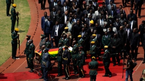Former Zimbabwean President Robert Mugabe's coffin arrives for a state funeral for at the National Sports Stadium in Harare, Saturday, Sept. 14, 2019. African heads of state and envoys are gathering to attend a state funeral for Mugabe, whose burial has been delayed for at least a month until a special mausoleum can be built for his remains. (AP Photo/Themba Hadebe)