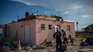 Silvia Nagy, 63, center, reacts while she talks with a firefighter arriving from the city of Miami to help those affected by Hurricane Dorian, in front of her destroyed house in Pelican Point, Grand Bahama, Bahamas, Monday, Sept. 9, 2019. Nagy and her husband retired to Pelican Point, Bahamas 3 years ago, had been traveling to the Bahamas for years and had lived through several storms, including Hurricane Francis. They never imagined that their lives 'work would be destroyed in an instant with the passing of Hurricane Dorian. (AP Photo / Ramon Espinosa)