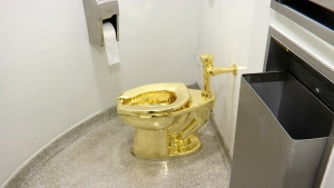 "This Sept. 16, 2016 file image made from a video shows the 18-karat toilet, titled ""America,"" by Maurizio Cattelan in the restroom of the Solomon R. Guggenheim Museum in New York. Thieves have stolen the solid gold toilet worth up to 1 million pounds from Blenheim Palace, the birthplace of Winston Churchill. The toilet, the work of Italian conceptual artist Maurizio Cattelan, had been installed only two days earlier at Blenheim Palace, west of London, after previously being on show at the Guggenheim Museum in New York. (AP Photo, File)"