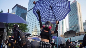 Anti-government protesters throw rocks near Central Government Complex in Hong Kong, Sunday, Sept. 15, 2019. Police fired a water cannon and tear gas at protesters who lobbed Molotov cocktails outside the Hong Kong government office complex Sunday, as violence flared anew after thousands of pro-democracy supporters marched through downtown in defiance of a police ban. (AP Photo/Vincent Yu)