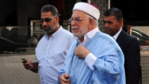 Ennahdha's presidential candidate Abdelfattah Mourou, center, arrives to cast his ballot at a polling station during the first round of the presidential election, in La Marsa, outside Tunis, Tunisia, Sunday Sept. 15, 2019. Tunisians are casting ballots in their North African country's second democratic presidential election, choosing among 26 candidates for a leader who can safeguard its young democracy and tackle its unemployment, corruption and economic despair. (AP Photo/Hassene Dridi)