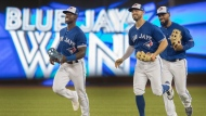 Toronto Blue Jays outfielders Randal Grichuk (centre), Teoscar Hernandez (right) and Jonathan Davis (left) come off the field celebrating defeating the New York Yankees in their American League baseball game in Toronto Sunday, September 15, 2019. THE CANADIAN PRESS/Fred Thornhill