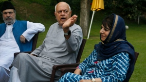 In this Aug. 4, 2019, file photo, National Conference president Farooq Abdullah, center, gestures during an all parties meeting in Srinagar, Indian controlled Kashmir. Abdullah, 81, also the former chief minister of Jammu and Kashmir, was arrested Monday under the Public Safety Act at his residence in Srinagar, the summer capital of the disputed region. (AP Photo/Mukhtar Khan, File)