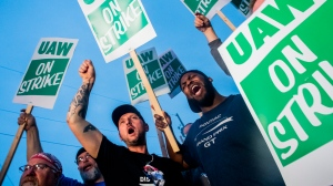 General Motors employees Bobby Caughel, left, and Flint resident James Crump, shout out as they protest with other GM employees, United Auto Workers members and labor supporters outside of the Flint Assembly Plant on Monday, Sept. 16, 2019 in Flint, Mich. (Jake May/The Flint Journal via AP)