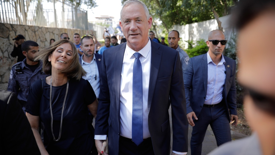 Blue and White party leader Benny Gantz and his wife Revital leave polling station in Rosh Haayin, Israel, Tuesday, Sept. 17, 2019. (AP Photo/Sebastian Scheiner)