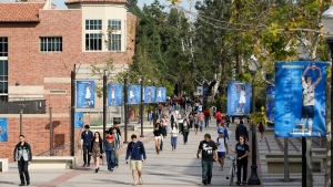 In this Feb. 26, 2015, file photo, students walk on the University of California, Los Angeles campus. Xiaoning Sui, 48, of Surrey, British Columbia, is accused of paying $400,000 to get her son into the University of California, Los Angeles, as a fake soccer recruit. She has become the 52nd person charged in a sweeping college admissions bribery scheme, according to an indictment unsealed Tuesday, Sept. 17, 2019, in Boston's federal court. (AP Photo/Damian Dovarganes, File)