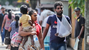 Sri Lankans walk past the National Hospital during a day long token strike by the members of Government Medical Officers Association in Colombo, Sri Lanka, Wednesday, Sept. 18, 2019. The trade union action is to demand the government resolve salary anomalies faced by the doctors serving at state-run hospitals. (AP Photo/Eranga Jayawardena)
