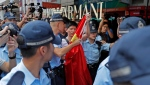A pro-China supporter, holding a Chinese national flag at center, is escorted by police officers in a shopping mall in Hong Kong, Wednesday, Sept. 18, 2019. Activists involved in the pro-democracy protests in Hong Kong appealed to U.S. lawmakers Tuesday to support their fight by banning the export of American police equipment that is used against demonstrators and by more closely monitoring Chinese efforts to undermine civil liberties in the city. (AP Photo/Kin Cheung)