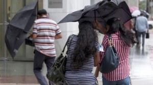 Pedestrians hold on to their umbrellas while a gust of wind blows at them at Fanning and Polk Streets as Tropical Storm Imelda makes its way across the Houston area during rush hour on Tuesday, Sept. 17, 2019, in downtown Houston. (Yi-Chin Lee/Houston Chronicle via AP)