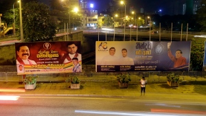 A Sri Lankan man stands near billboards displaying President Maithripala Sirisena, right, and former president Mahinda Rajapaksa, left, in Colombo, Sri Lanka, Wednesday, Sept. 18, 2019. (AP Photo/Eranga Jayawardena)