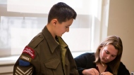 Grade 7 student Tristan Levesque tries on a Second World War era battle dress jacket as classmate Olivia Puff looks on at their middle school in Saint John, N.B. The clothing is one of several items in a kit provided free of charge to schools by the Canadian War Museum focusing on Canada's role in the Second World War. THE CANADIAN PRESS/HO-Canadian War Museum
