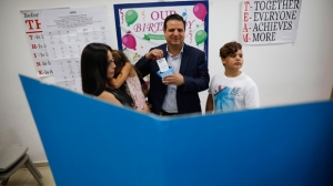 In this Tuesday, Sept. 17, 2019 file photo, Israeli Arab politician Ayman Odeh casts his vote in Haifa, Israel, Tuesday, Sept. 17, 2019. Israel's Arab coalition appears poised to emerge as the main opposition bloc following Tuesday's vote. The historic first would grant a new platform to a long-marginalized minority and the only major political movement still pushing for peace with the Palestinians. (AP Photo/Ariel Schalit)