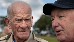Tom Rice, a 98-year-old American WWII veteran, left, and U.S. ambassador Pete Hoekstra talks to journalists after both landed with a tandem parachute jump near Groesbeek, Netherlands, Thursday, Sept. 19, 2019, as part of commemorations marking the 75th anniversary of Operation Market Garden. Rice jumped with the U.S. Army's 101st Airborne Division in Normandy, landing safely despite catching himself on the exit and a bullet striking his parachute. (AP Photo/Peter Dejong)