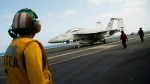 In this June 3, 2019, photo, a crew member looks at a taxing F/A-18 fighter jet on the deck of the USS Abraham Lincoln aircraft carrier in the Persian Gulf. The U.S. aircraft carrier the White House ordered to the Mideast over a perceived threat from Iran remains outside of the Persian Gulf amid efforts to de-escalate tensions between Tehran and Washington. (AP Photo/Jon Gambrell)