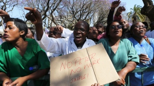 Zimbabwean medical staff march on the streets of Harare, Thursday Sept. 19, 2019. Zimbabwean doctors protesting the alleged abduction of a union leader won a High court ruling allowing them to march and handover a petition to the parliament.The Zimbabwe Hospital Doctors Association has said its president, Peter Magombeyi, was abducted on Saturday after calling for a pay strike, and members say they will not return to work until he is found. (AP Photo/Tsvangirayi Mukwazhi)