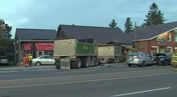 Police are investigating after a dump truck collided with vehicles and into a building in Caledon.
