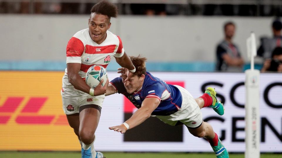 Japan's Kotaro Matsushima, left, fends off Russia's Vladislav Sozonov to score his third try during the Rugby World Cup Pool A game at Tokyo Stadium between Russia and Japan in Tokyo, Japan, Friday, Sept. 20, 2019. (AP Photo/Jae Hong)