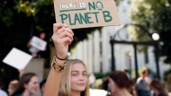 A demonstrators holds up a sign while taking part in the global climate strike at the University of Georgia Arch Friday, Sept. 20, 2019 in Athens, Ga. (Joshua L. Jones/Athens Banner-Herald via AP)