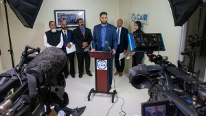 In this Thursday, Sept. 19, 2019 photo, Imam Omar Suleiman, center, speaks during a press conference at the Council on American-Islamic Relations DFW office in Dallas regarding a profiling incident where two Muslims from North Texas said they experienced during a recent American Airlines flight in Alabama. CAIR is calling on the airline to investigate the incident and implement corrective action to those involved. (Lynda M. Gonzalez/The Dallas Morning News via AP)