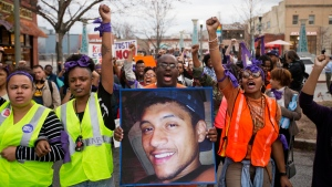 In this March 11, 2015 file photo, Brandon Marshall carries a photo of Anthony Hill as protesters march through the street demonstrating Hill's shooting death by a police officer, in Decatur, Ga.  Robert Olsen, then a DeKalb County police officer, shot and killed 27-year-old Anthony Hill in March 2015. Olsen was indicted on charges including felony murder. Jury selection for his trial is scheduled to start Monday, Sept. 23, 2019.   (AP Photo/David Goldman, File)