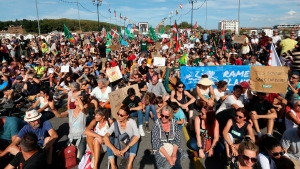Protestors sit on the ground as they take part in a climate demonstration, in Bayonne, Saturday, Sept. 21, 2019. President Emmanuel Macron has often presented himself as a champion of environment, but climate activists described his actions as mere grandstanding, charging that Macron has failed to take concrete measures at home to fight climate change. (AP Photo/Bob Edme)