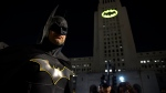 "FILE - In this June 15, 2017 file photo, Tony Bradshaw, of Los Angeles, dressed as Batman, poses in front of a Bat-Signal projected onto City Hall during a tribute to ""Batman"" star Adam West in Los Angeles. The night sky all over the world is lighting up Saturday, Sept. 21, 2019, with an illumination of the famed bat insignia to mark a special anniversary for Batman. DC Comics is carrying off a celebration of ""Batman Day"" to mark the 80th anniversary of the appearance of crimefighter Bruce Wayne and his masked hidden identity. Fan gatherings are planned all over the world. (Photo by Chris Pizzello/Invision/AP, File)"