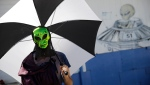 "Seth Unterseher holds an umbrella for shade while wearing an alien mask at an event at the Little A'Le'Inn inspired by the ""Storm Area 51"" internet hoax Saturday, Sept. 21, 2019, in Rachel, Nev. (AP Photo/John Locher)"