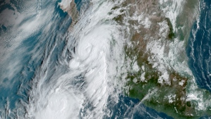 This GOES-16, GeoColor satellite image taken Friday, Sept. 20, 2019, at 14:50 UTC and provided by National Oceanic and Atmospheric Administration (NOAA), shows Hurricane Lorena, top center, followed by Tropical Storm Mario, near the southern tip of Mexico's Baja California peninsula. (NOAA via AP)