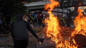 A protester sets fire to a barricade during a protest in Hong Kong on Sunday, Sept. 22, 2019. Hong Kong's pro-democracy protests, now in their fourth month, have often descended into violence late in the day and at night. A hardcore group of protesters says the extreme actions are needed to get the government's attention. (AP Photo/Vincent Yu)
