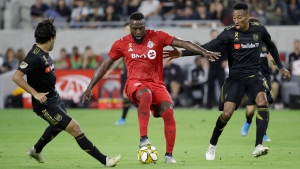 Toronto FC's Jozy Altidore, center, is defended by Los Angeles FC's Carlos Vela, left, and Mark-Anthony Kaye during the first half of an MLS soccer match Saturday, Sept. 21, 2019, in Los Angeles. (AP Photo/Marcio Jose Sanchez)
