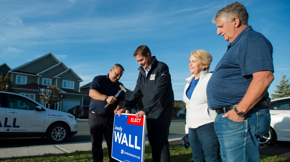Federal Conservative leader Andrew Scheer, second left, and Conservative MP candidate Joedy Wall, right, hammer in a sign on homeowners Beth Noseworthy, second right, and her husband Doug's front lawn, in St. John's on Sunday, September 22, 2019. THE CANADIAN PRESS/Nathan Denette