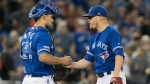 Toronto Blue Jays catcher Luke Maile, left, shakes hands with pitcher Ken Giles after they defeated the Baltimore Orioles in their American League MLB baseball game in Toronto on Wednesday, September 25, 2019. THE CANADIAN PRESS/Fred Thornhill