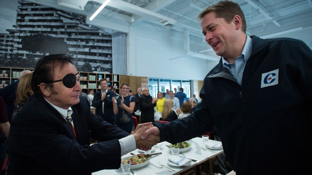 Federal Conservative leader Andrew Scheer, right, greets people at an Italian restaurant during a campaign stop in Montreal on Thursday, September 26, 2019. THE CANADIAN PRESS/Nathan Denette