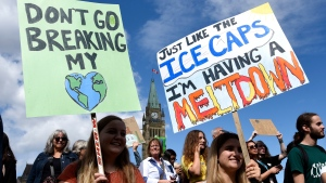 People rally on Parliament Hill in Ottawa as part of a Global Climate Strike, protesting against climate change and inaction, on Friday, Sept. 27, 2019. (THE CANADIAN PRESS/Justin Tang)