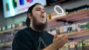 Retail analysts say the growing move to ban flavoured e-cigarettes over health concerns could actually benefit convenience stores. Devin Lambert, the manager at Good Guys Vape Shop, demonstrates to blow a vapor ring while using an e-cigarette in Biddeford, Maine, Tuesday, Sept. 3, 2019. THE CANADIAN PRESS/AP-Robert F. Bukaty
