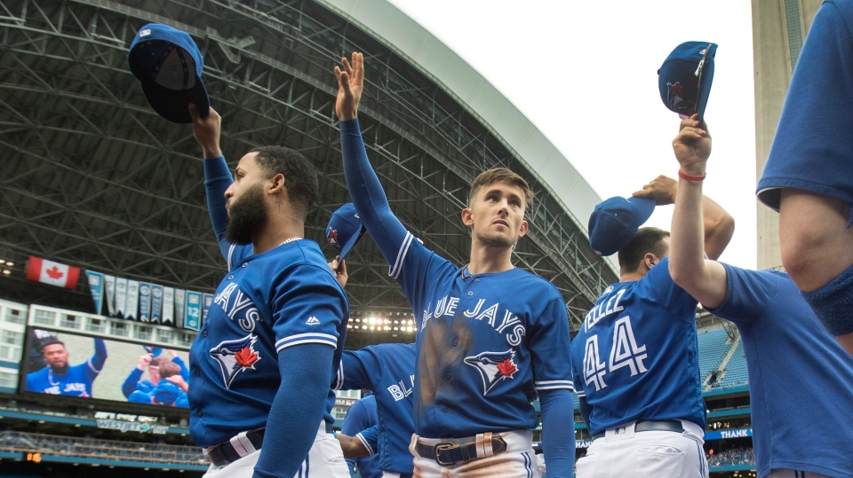 Toronto Blue Jays players including Cavan Biggio (second from left) tip their hats to fans during the middle of third inning of their American League MLB baseball game against the Tampa Bay Rays in Toronto, Sunday, September 29, 2019. THE CANADIAN PRESS/Fred Thornhill