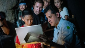"In this Nov. 14, 2018, photo provided by De Warrenne Pictures, director Tom Waller, right, talks to actors for a scene of his film ""The Cave"" in Thailand. It was a story that gripped the world: determined divers racing time and the elements to rescue 12 boys and their soccer coach trapped for more than two weeks in a flooded cave deep inside a northern Thai mountain. (De Warrenne Pictures via AP)"